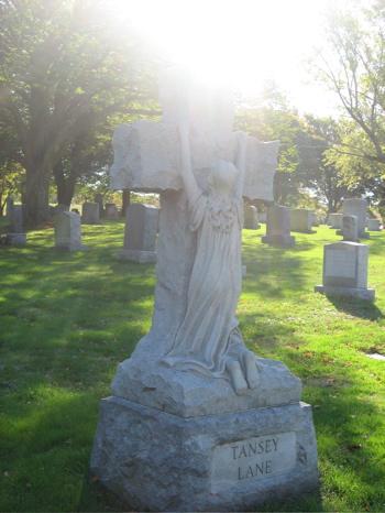 tombstone, kneeling at cross